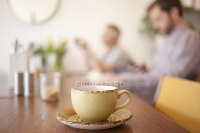 Cup on table and people in background in a cafe — Stock Photo