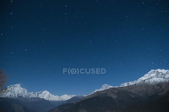 Cordillera nevada bajo cielo estrellado nocturno, Nepal - foto de stock