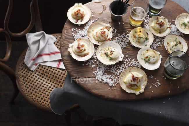 Vista dall'alto delle capesante cotte in conchiglie sul tavolo — Foto stock