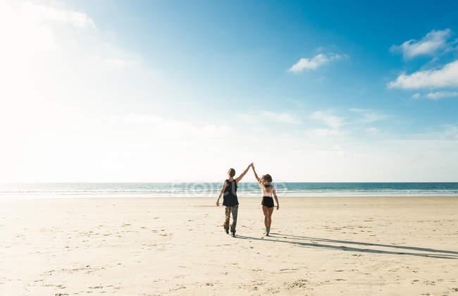 Молодая пара, ходить на пляж Сан-Диего, взявшись за руки с поднятыми — стоковое фото