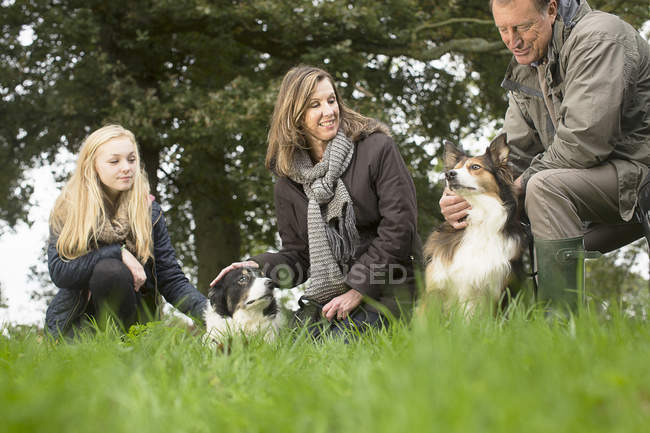 Senior couple and granddaughter out with dogs — Stock Photo