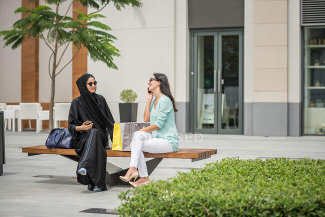 Young middle eastern woman wearing traditional clothing sitting on bench with female friend, Dubai, United Arab Emirates — Stock Photo