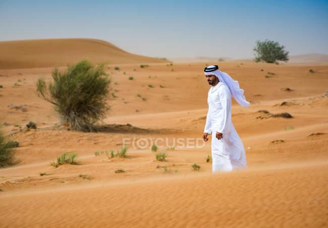 Nahen Ostens Mann Tracht gehen in Wüste, Dubai, Vereinigte Arabische Emirate — Stockfoto