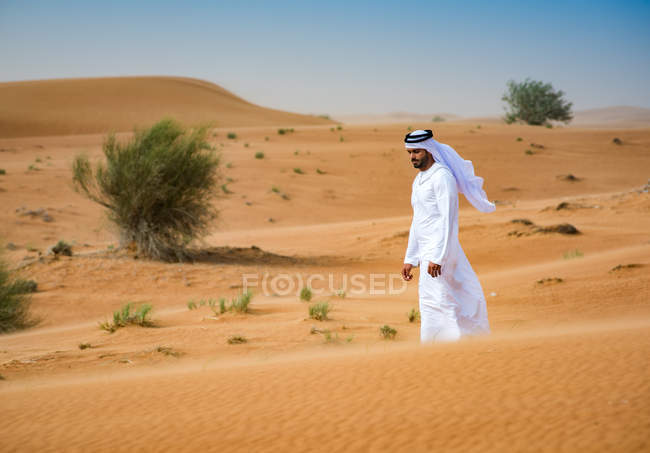 Middle eastern man wearing traditional clothes walking in desert, Dubai, United Arab Emirates — Stock Photo