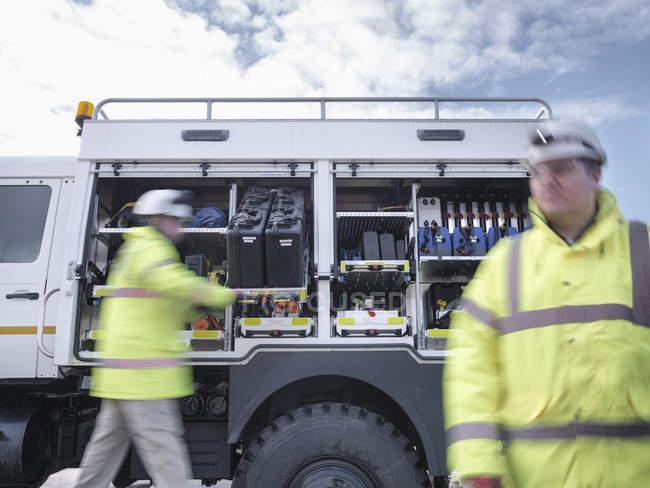 Сотрудники аварийно-спасательной службы со специальным оборудованием и спасательным грузовиком — стоковое фото