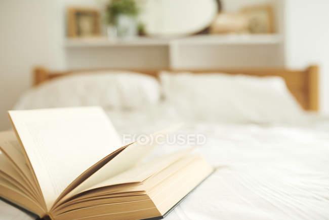 Chiuda sul colpo di un libro aperto sul letto — Foto stock