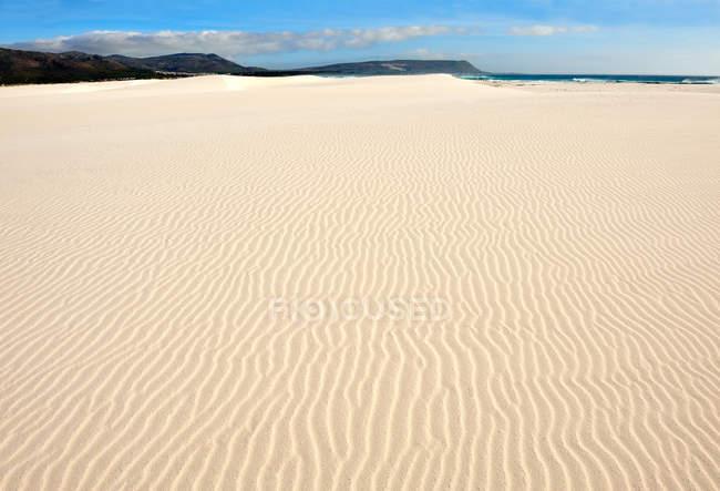 Rippled sand on beach with blue cloudy sky — Stock Photo
