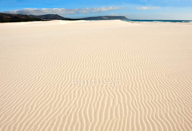 Rippled sand on beach with blue cloudy sky — Stock Photo