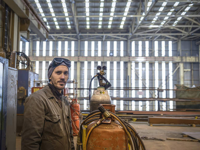 Portrait of welder wearing overalls and safety goggles in factory — Stock Photo