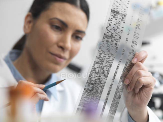 Female scientist examining DNA gel in laboratory for genetic research — Stock Photo