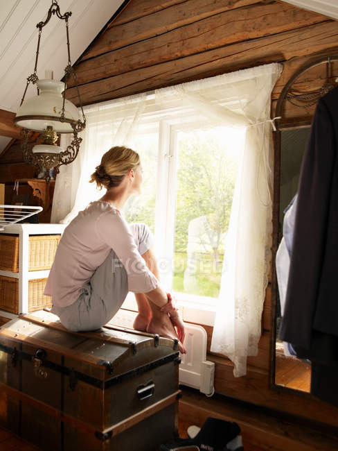 Businesswoman sitting on trunk at window in house — Stock Photo