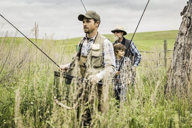 Multi generation family in field carrying fishing rods — Stock Photo