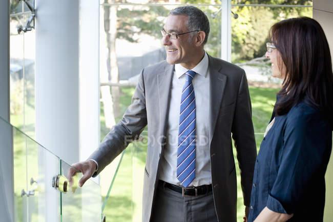 Empresário e mulher olhando para fora do prédio de escritórios — Fotografia de Stock
