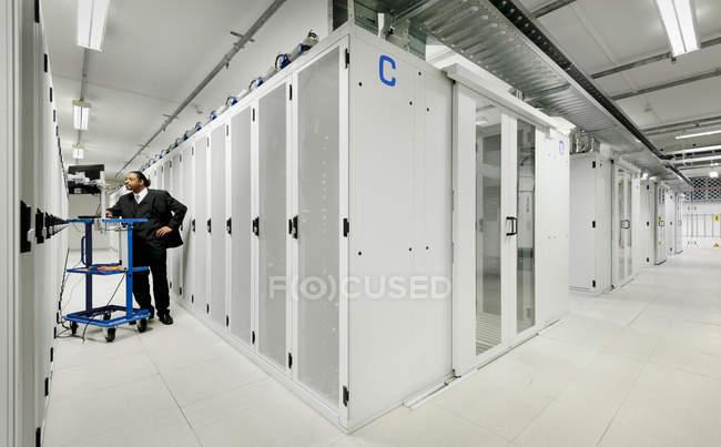 Empresário usando computador com servidores — Fotografia de Stock