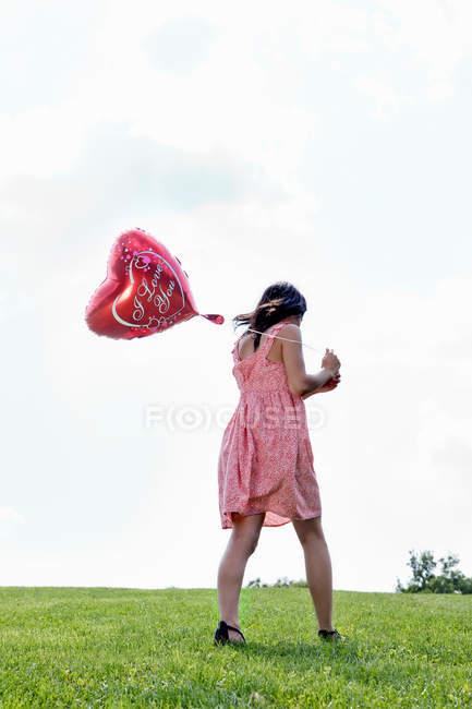 Teenager carrying heart-shaped balloon — Stock Photo