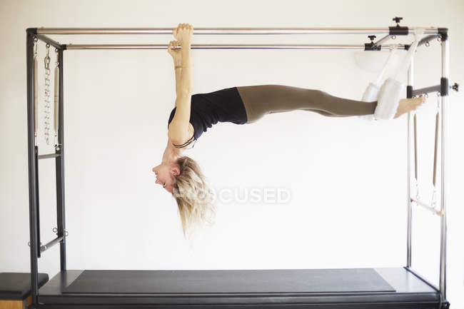 Femme mure pratiquant le pilates sur table trapèze en gym pilates — Photo de stock