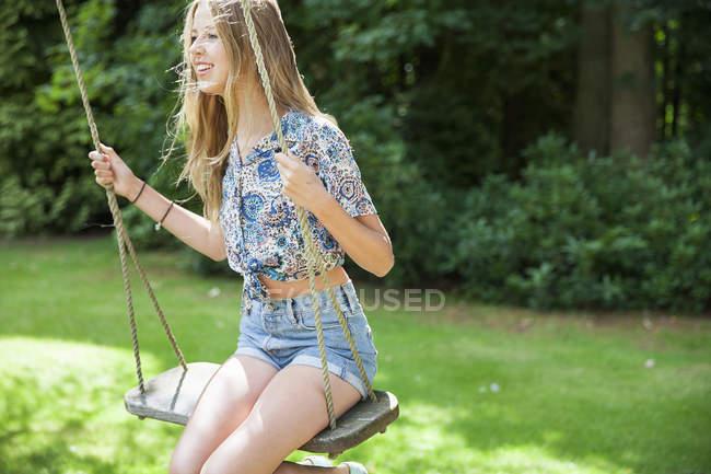 Teenage girl on swing in green summer garden — Stock Photo
