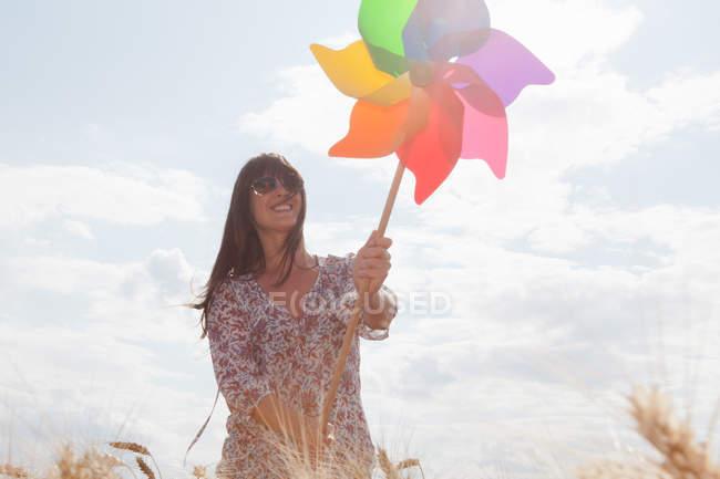 Metà donna adulta che tiene mulino a vento — Foto stock