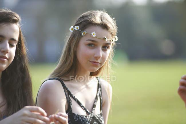 Портрет девочки-подростка в головном уборе из ромашки в парке — стоковое фото
