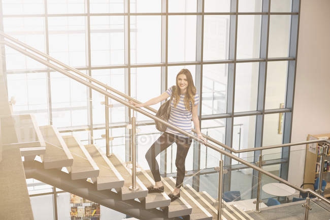 Young woman standing on staircase — Stock Photo