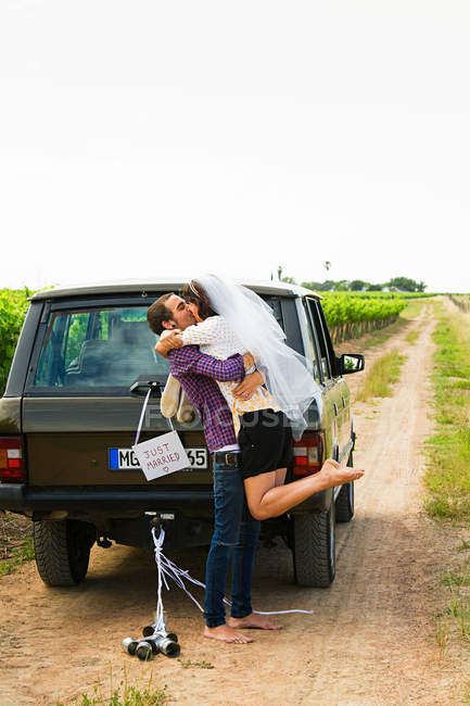 Pareja de recién casados besándose por vehículo - foto de stock
