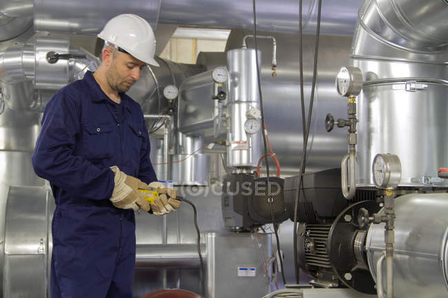 Técnico de monitoreo de cableado de tuberías en la central eléctrica - foto de stock