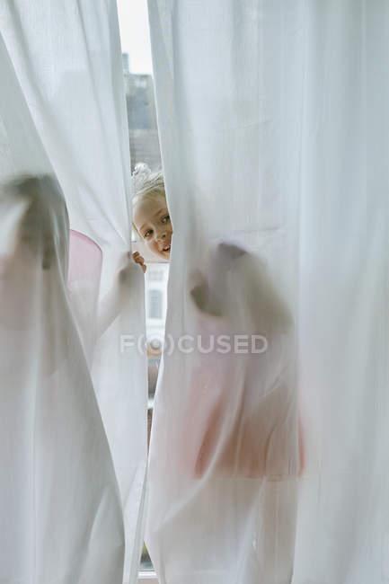 Девушка заглядывает через занавеску — стоковое фото