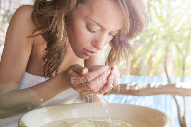 Young woman with cupped hands cleansing face over bowl at spa — Stock Photo