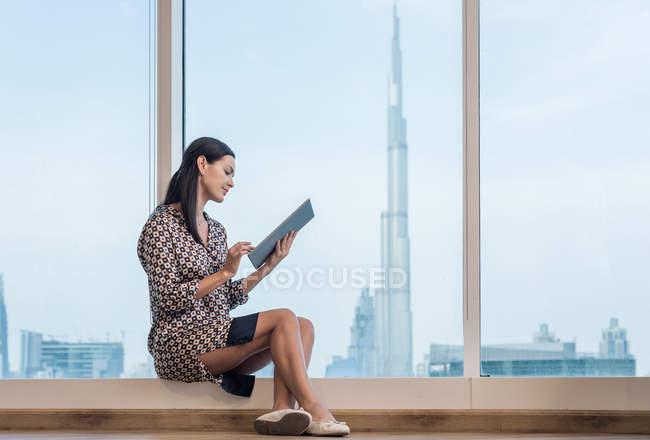 Бизнесвумен с цифровым планшетом, сидящая у окна, Дубай, ОАЭ — стоковое фото