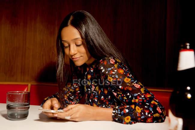 Mulher sentada em madeira com painéis de cabine olhando para smartphone sorrindo — Fotografia de Stock