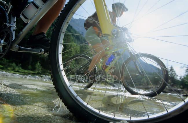 Persone che attraversano il flusso in bicicletta — Foto stock