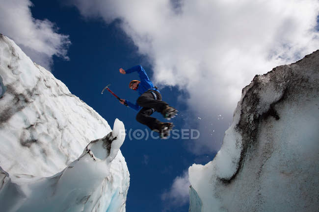 Hiker jumping in between glaciers — Stock Photo