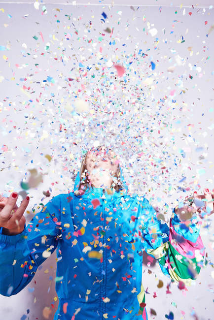 Studio shot of young woman and explosion of confetti — Stock Photo