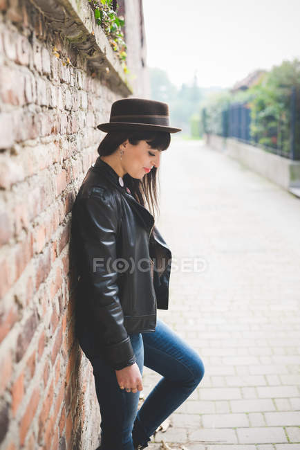 Young woman leaning against brick wall — Stock Photo
