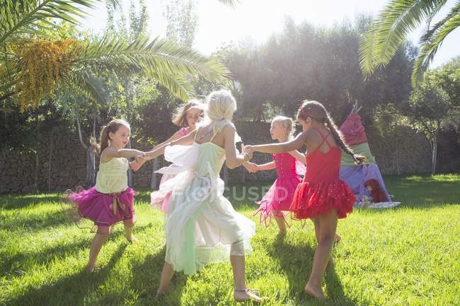 Five energetic girls in fairy costumes playing in garden — Stock Photo