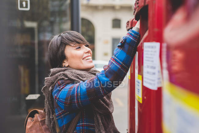 Young woman posting letter — Stock Photo