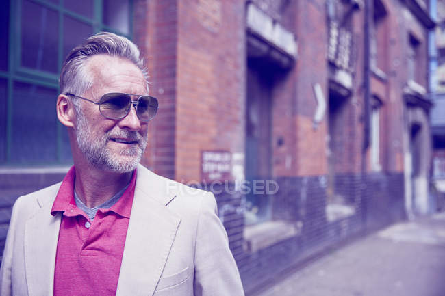 Mature man walking along street, looking away — Stock Photo