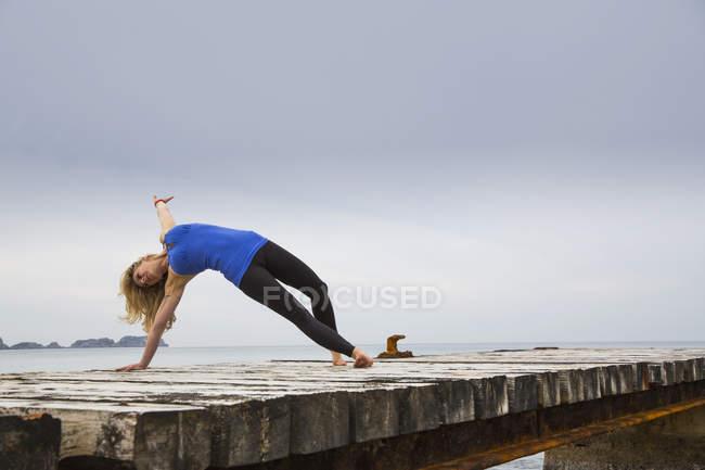 Femme adulte moyenne pratiquant le yoga se déplacer sur jetée de mer en bois — Photo de stock