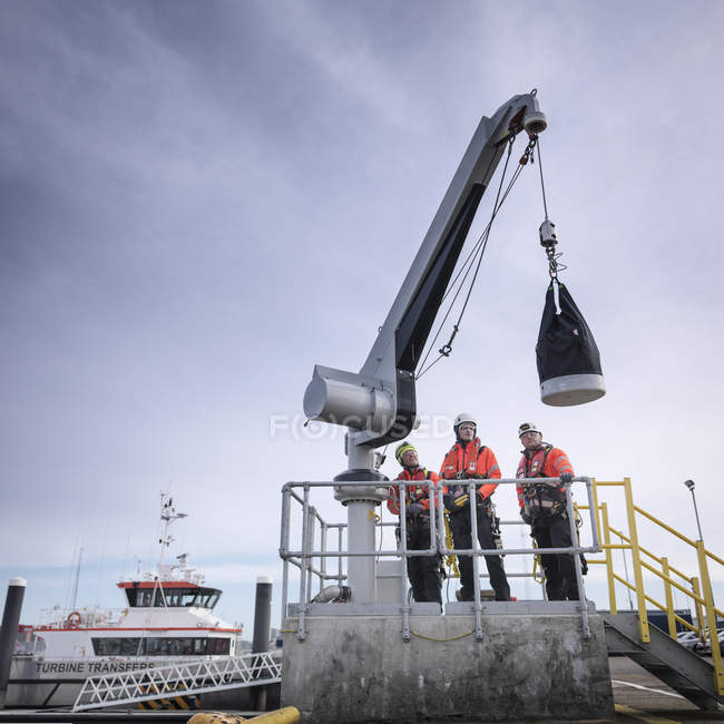 Ingenieros de parques eólicos marinos en puerto con grúa - foto de stock