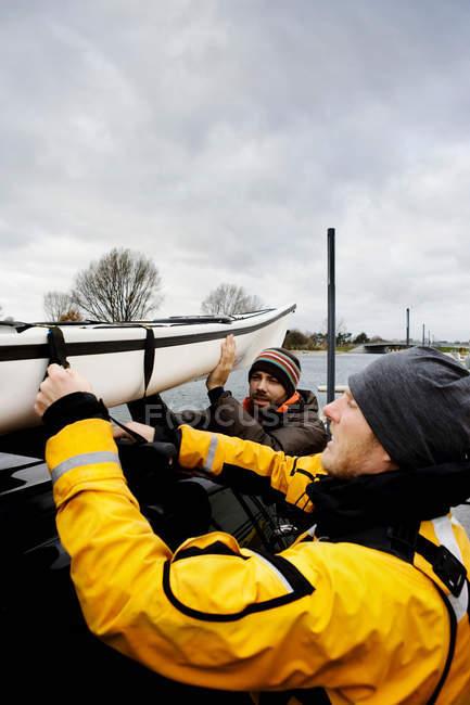 Мужчины грузят каяк в машину — стоковое фото
