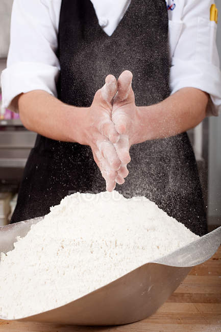 Male chef rubbing flour on hands in commercial kitchen — Stock Photo