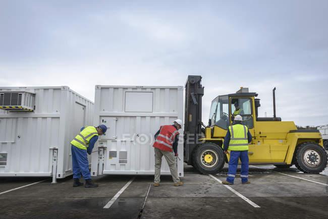 Сотрудники аварийно-спасательной группы устанавливают аварийные диспетчерские с помощью погрузчика — стоковое фото
