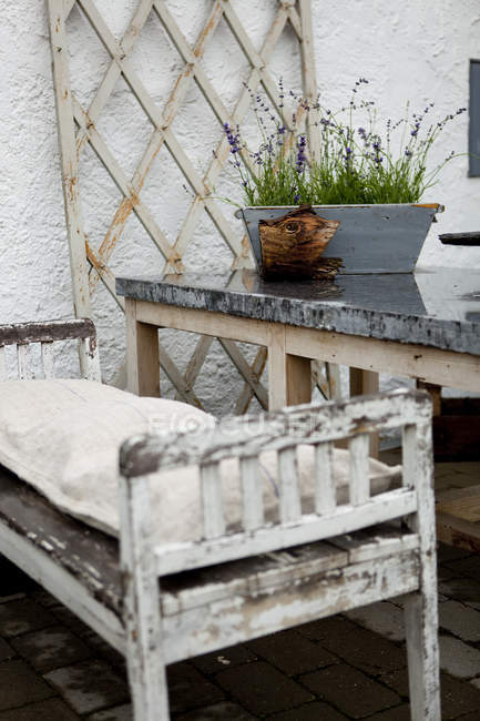 Rustic bench and plant pot on terrace in rain — Stock Photo