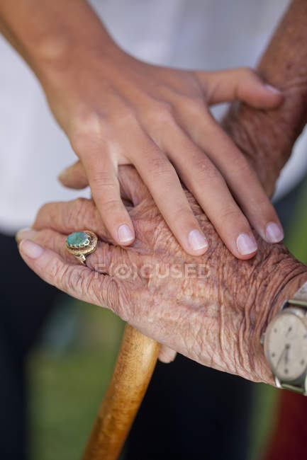 Close up of care assistants hand reassuring senior woman — Stock Photo
