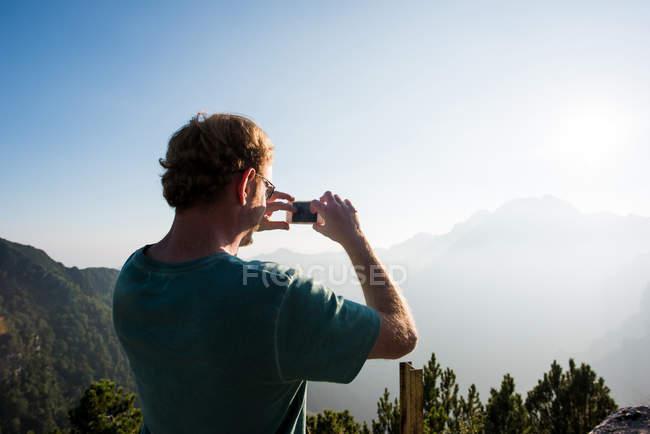Вид сзади на человека, фотографирующего горы, Пассо-Манива, Италия — стоковое фото