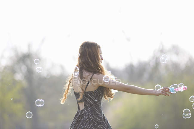 Teenage girl spinning bubbles with bubble wand in park — Stock Photo