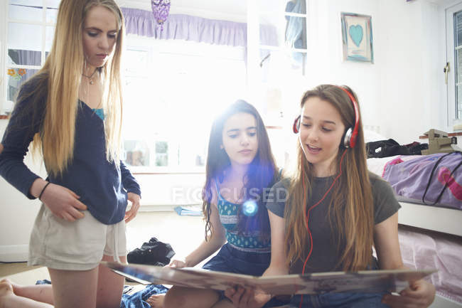 Три девочки-подростка смотрят на обложку виниловой пластинки в спальне — стоковое фото