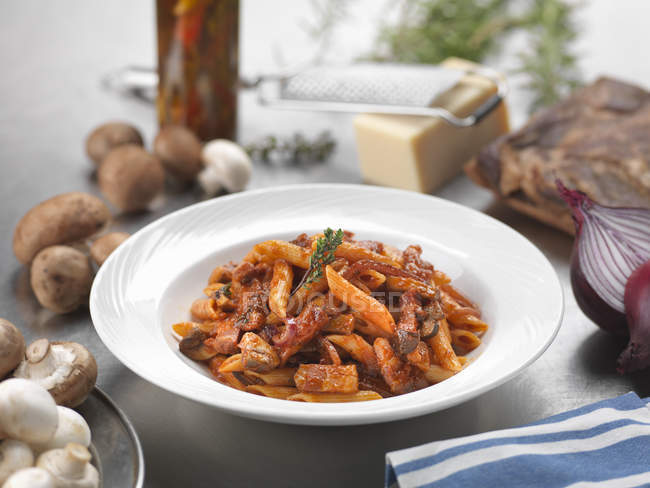 Traditional Italian meal pasta alla boscaiola in plate on table — Stock Photo