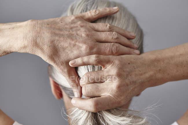 Vue arrière de la femme tirant les cheveux gris en queue de cheval — Photo de stock