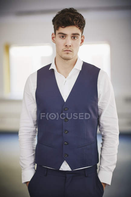 Portrait of man wearing waist coat, hands in pockets looking at camera — Stock Photo